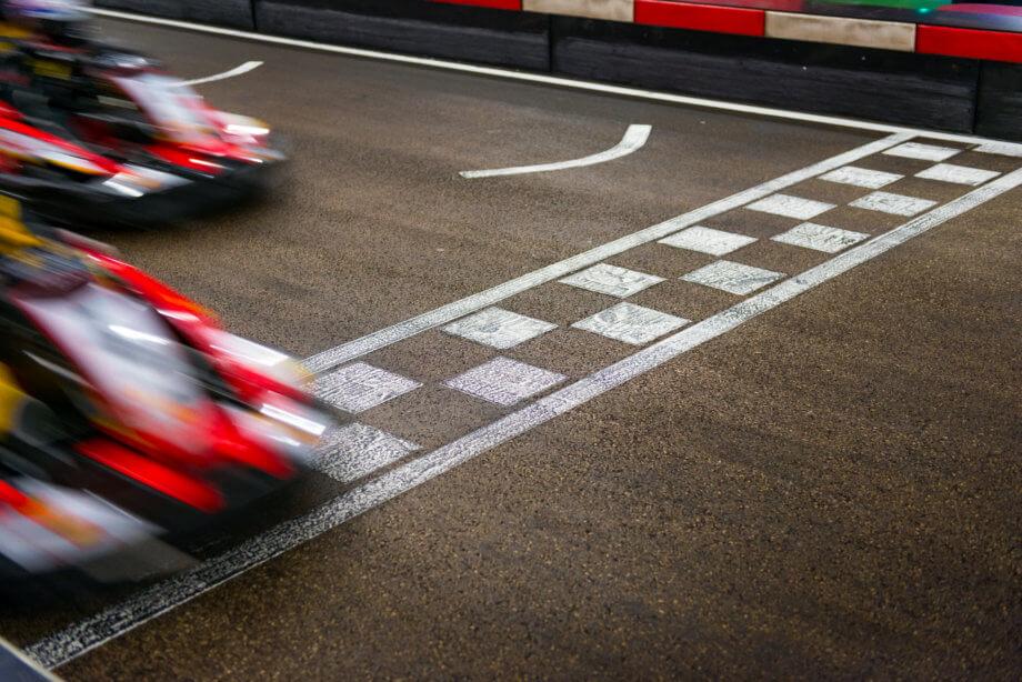Autorennen bei dem ein Rennwagen vor dem anderen über die Ziellinie fährt.