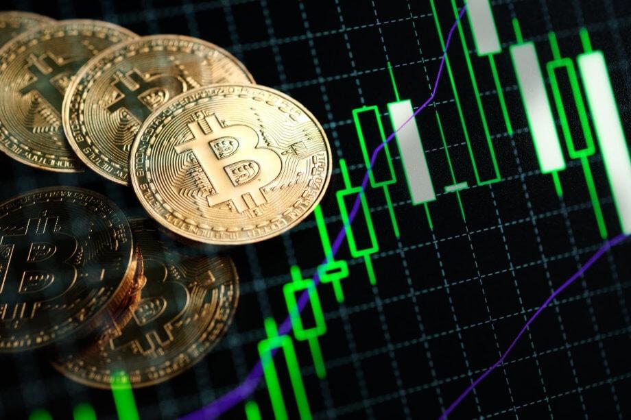 bitcoin-münzen-liegen-auf-einer-chart-mit-grünen-kerzen
