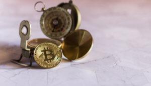 bitcoin-münze-liegt-auf-einem-kompass