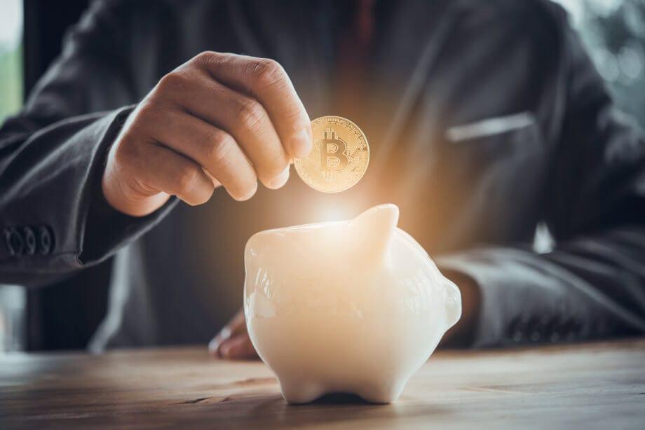 bitcoin-münze die jemand in ein sparschwein wirft das leuchtet