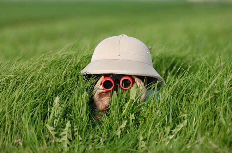 Ein kleiner Junge mit Safari-Hut und Sonnenbrille lauert im hohen Gras