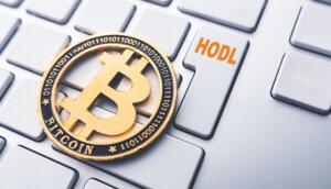 Bitcoin Münze auf Tastertur mit HODL Schriftzug