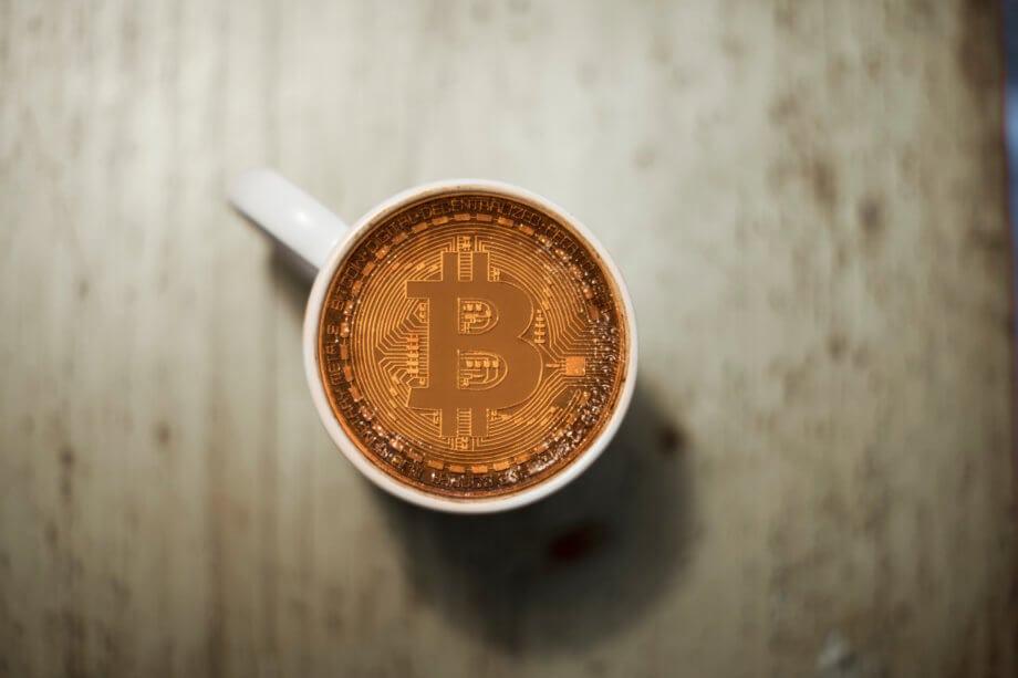 eine bitcoin-münze in einer kaffetasse