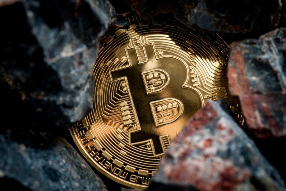 bitcoin-münze unter Steinen