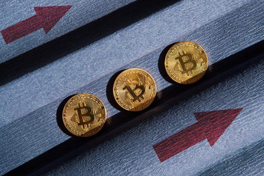 drei goldene bitcoin-münzen, daneben zwei rote pfeile, die nach rechts oben zeigen