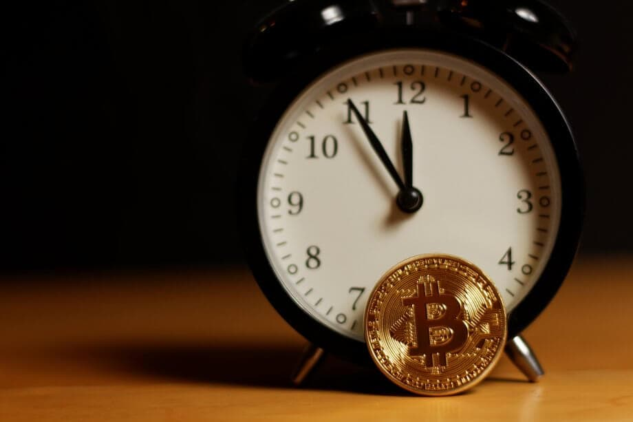 Ein Wecker, bei dem die Zeiger auf 5 vor 12 stehen und davor steht eine bitcoin-münze