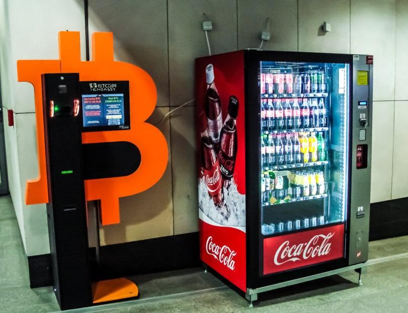 Ein Bitcoin-Automat steht neben einem Coca-Cola-Automat