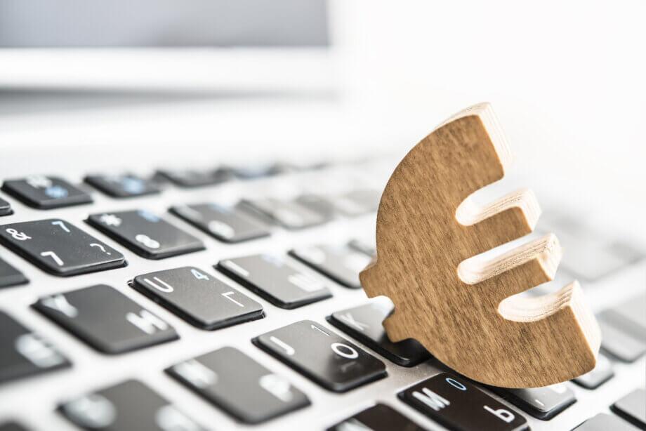 ein hölzernes euro symbol, das auf einer tastatur liegt