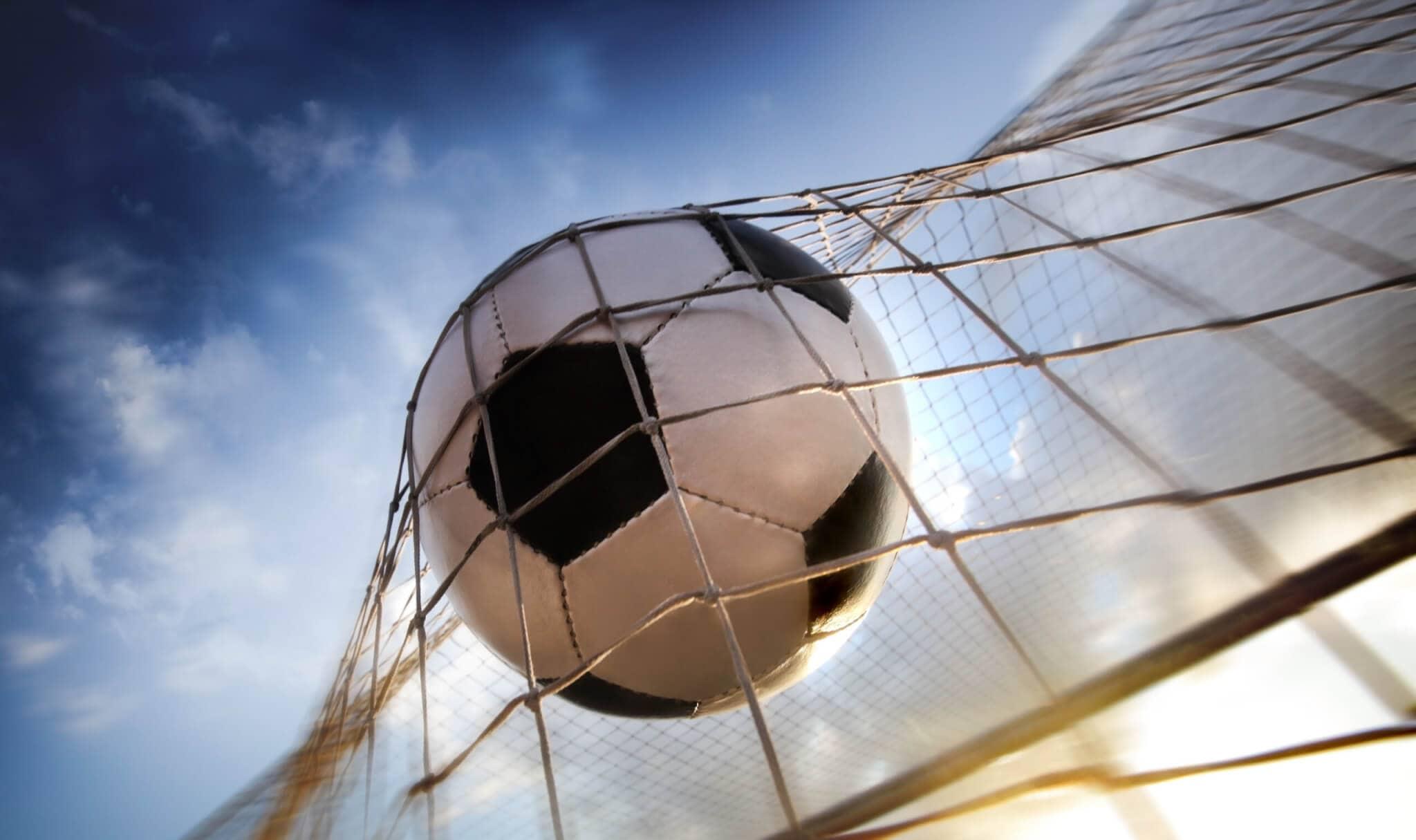 ein fußball, der ins netz fliegt