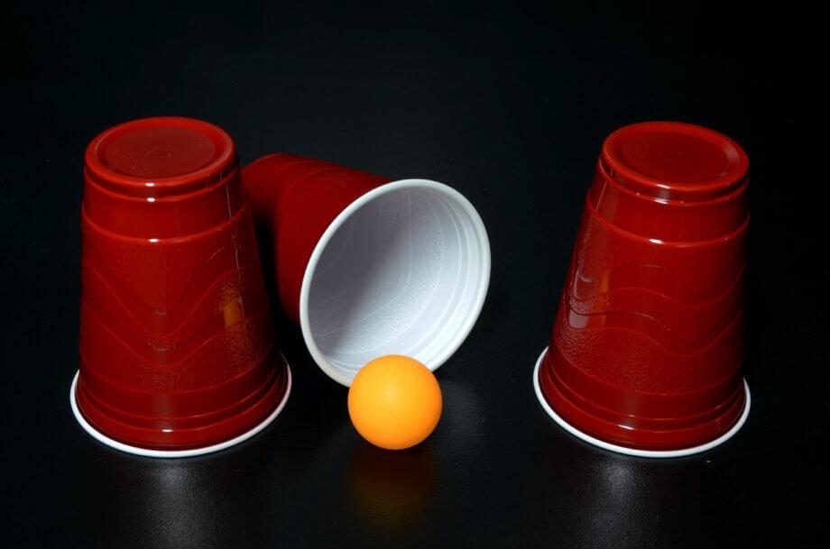ball-liegt-vor-einem-umgekippten-becher-neben-anderen-nicht-umgekippten-bechern