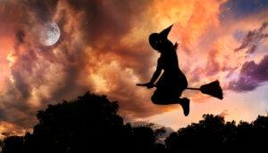 Silhoutte einer Hexe, die ihm Gegenlicht des Mondes auf einem Besen fliegt