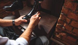 Ein Schuhputzer bürstet einen Herrenlederschuh