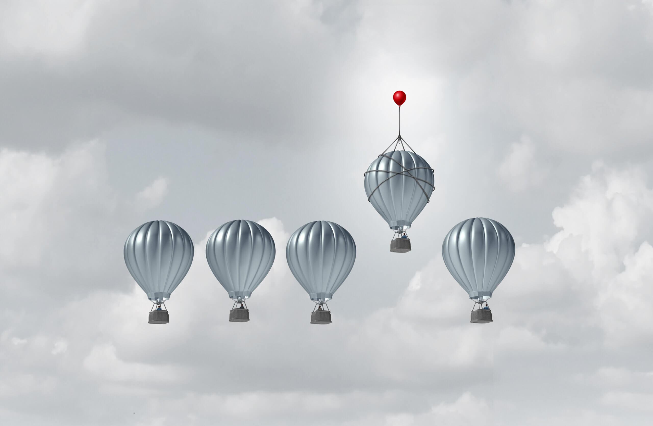 fünf graue heißluftballons, von denen sich der vierte von links von den anderen abhebt, indem er von einem roten kleineren ballon nach oben gezogen wird