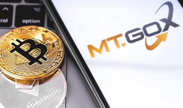 Montage mit Bitcoin- und Ethereum-Münze und Mt.Gox-Logo auf Smartphone-Display