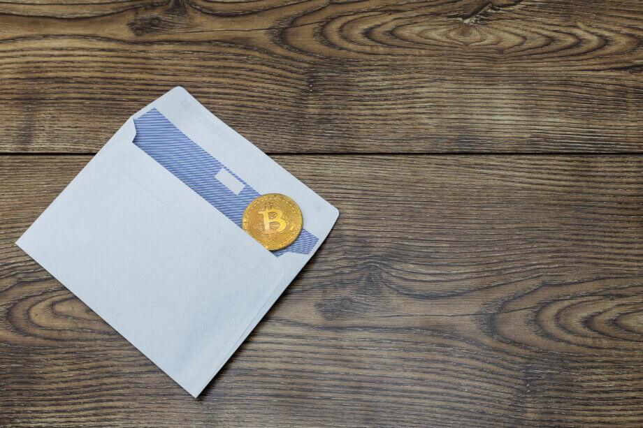 briefumschlag-mit-bitcoin-münze-auf-einem-holztisch