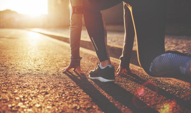 Läufer in Startposition und Sonne scheint entgegen auf Straße