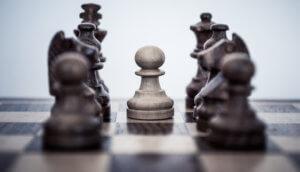 Auf einem Schachbrett ist ein Bauer von anderen Spielfiguren umzingelt, die institutionelle Investoren darstellen sollen.