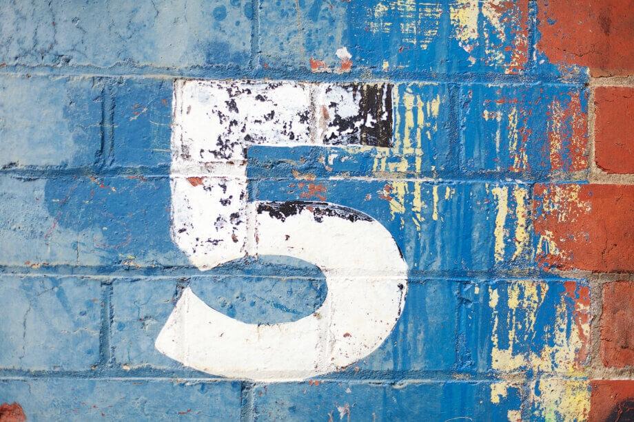 Die Zahl fünf auf einer blauen Wand (BTC)