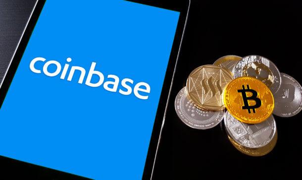 Smartphone mit Coinbase-Logo neben einem Stapel (Krypto-)Münzen