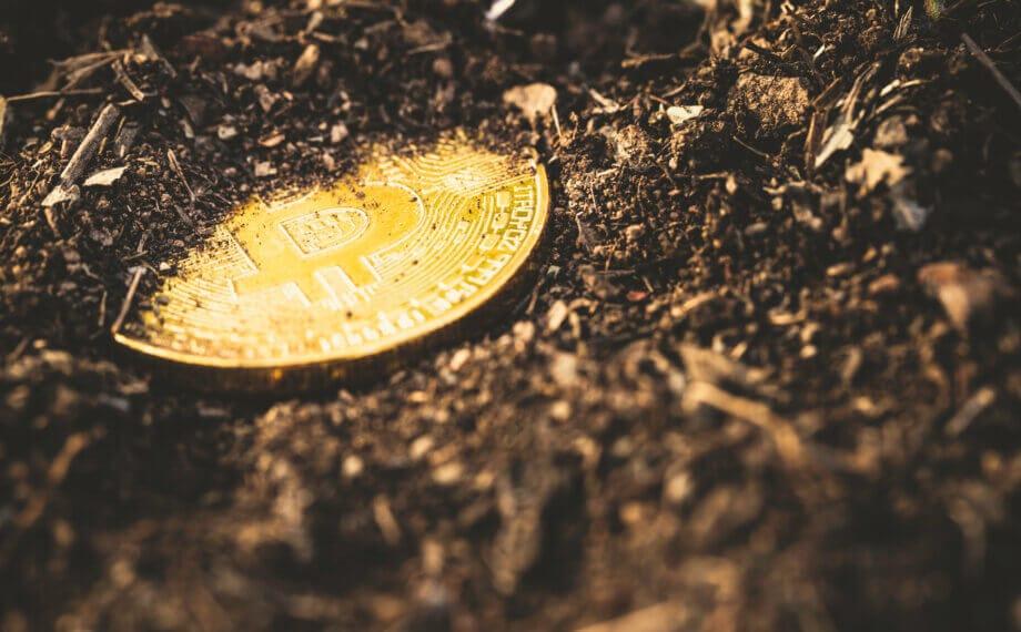 Teilweise vergrabene Bitcoin-Münze