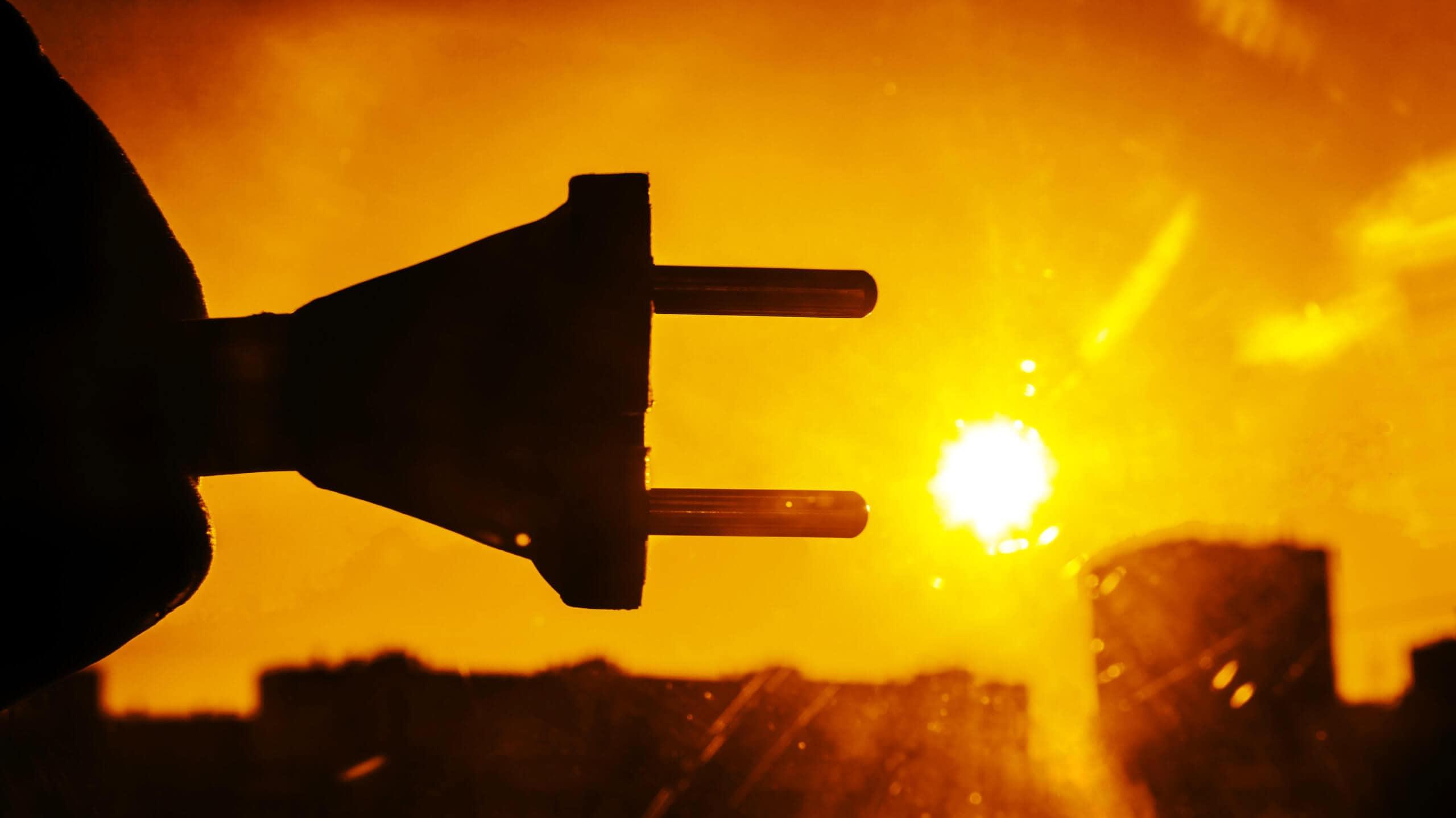 Stromstecker wird in die Sonne gehalten.