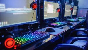 Mehrere Gaming-Computer stehen in einem Internetcafe nebeneinander und die Tastaturen leuchten bunt.