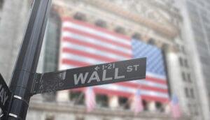 ein straßenschild mit der aufschrift wall st, im hintergrund eine amerikanische Flagge