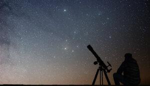 ein mann der vor einem teleskop sitzt und damit in die sterne schaut