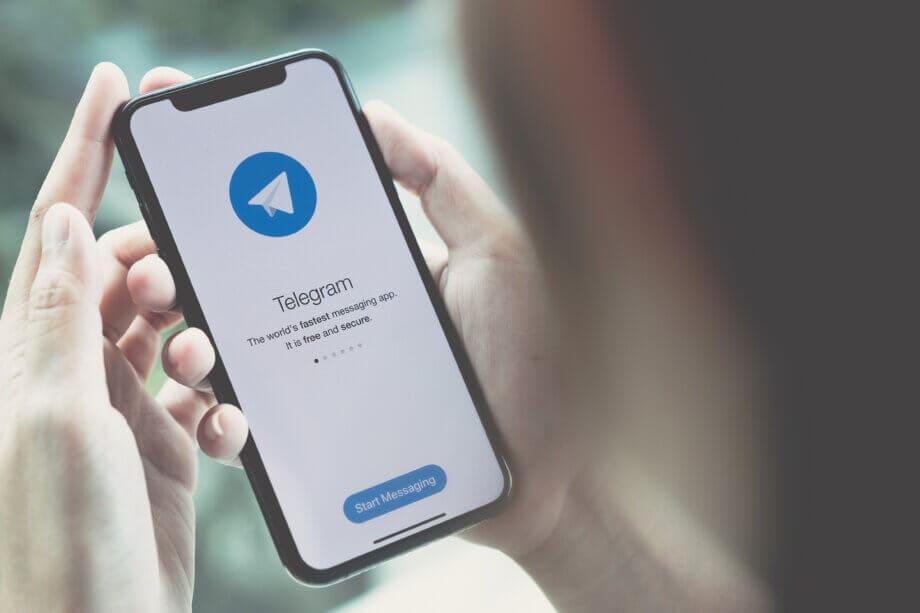 die telegram app auf einem smartphone, das von zwei händen gehalten wird