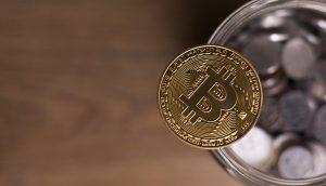Bitcoin-Münze liegta auf dem Rand eines Glases voller Kleingeld
