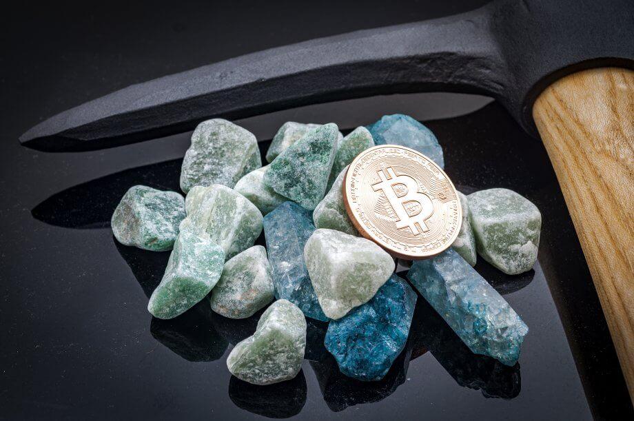 Steine und Bitcoin-Münze neben Spitzhacke