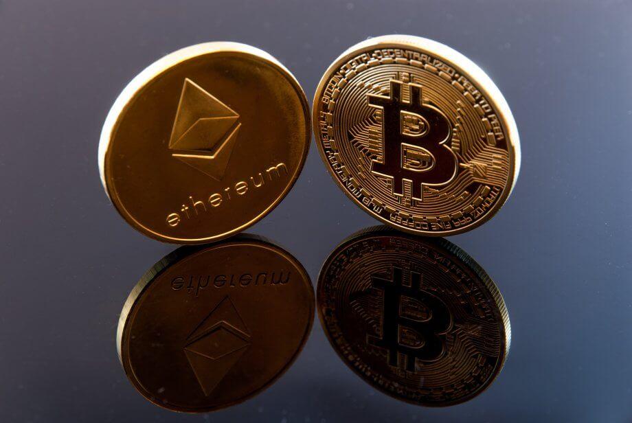 Ethereum-Münze und Bitcoin-Münze auf spiegelndem Untergrund.