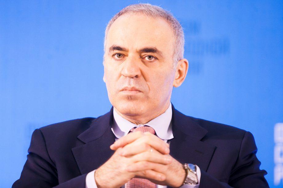 Kasparov-sitzt-vor-einem-blauen-hintergrund