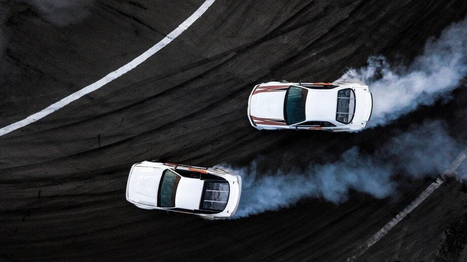 zwei weiße autos von oben, die voll am racen sind