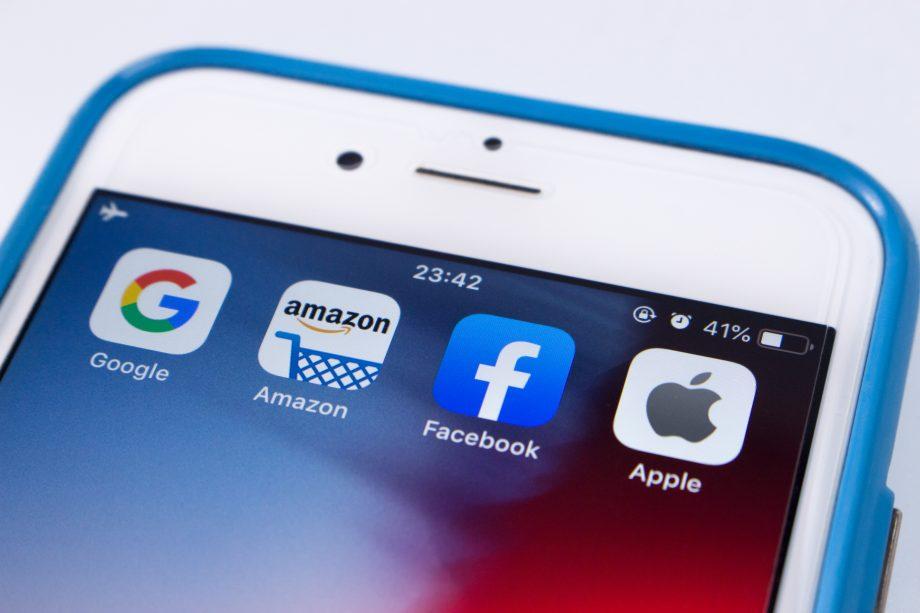 Die Symbole der Big Four: Google, Facebook, Amazon Apple auf einem smartphone als antithese zum bitcoin-system