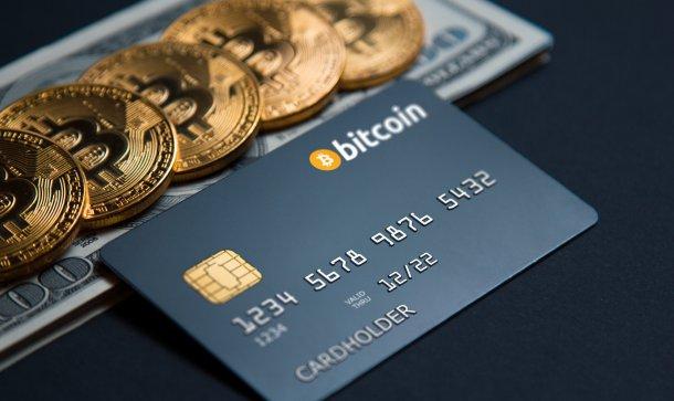 Kreditkarte mit Aufschrift Bitcoin liegt vor mit Bitcoin-Münzen bedecktem Dollarschein