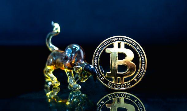 Bitcoin-Münze neben Bullen-Figur aus Glas