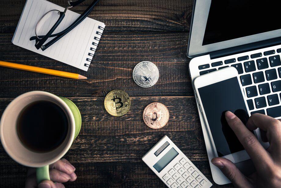 Bitcoin-Münzen nebst einer Kaffeetasse, einer Brille, einem Notizblock, einem Taschenrechner, einem Smartphone und einem Laptop