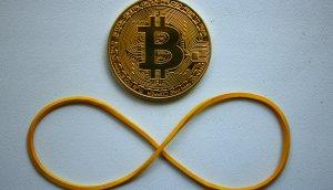 Bitcoin Münze mit Gummi, das zu einer liegenden Acht geformt wurde