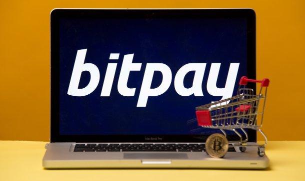 Laptop mit Bitpay-Logo auf dem Bildschirm und Miniatur-Einkaufswagen samt Bitcoin-Münue