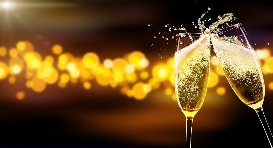 zwei gläser champagner die auf unscharem hintergrund anstoßen