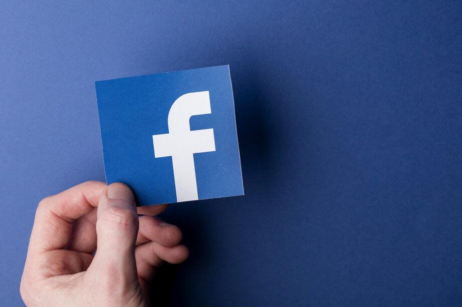 Das Facebook-Symbol von einer Hand gehalten auf blauem Hintergrund