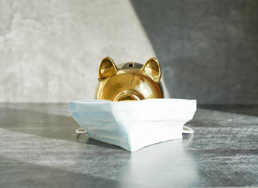 ein goldenes schwein hinter einer corona-atemschutzmaske