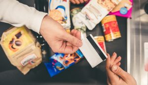 hände-übergeben-eine-kreditkarte-an-einer-kasse