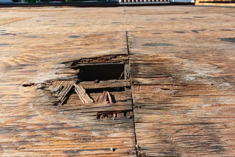 Sperrholzschädigung und Wasserflecken aus Regenwasser stehen, die auf dem Dach unweit des Abspaltungslochs auslaufen. Vorangehendes Projekt zur Prüfung, Reparatur und Erneuerung des Flachdachs.