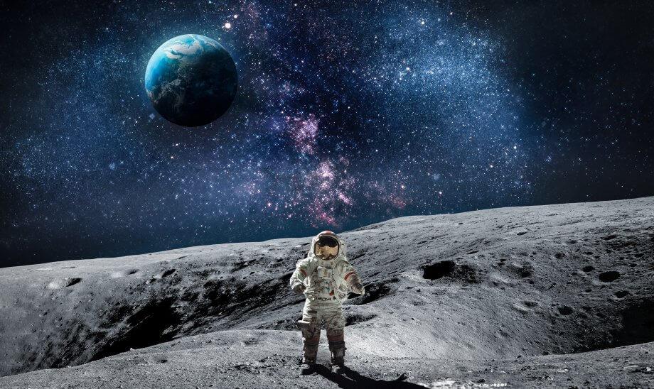 Ein Astronaut der auf dem Mond steht, im Hintergrund die Erde