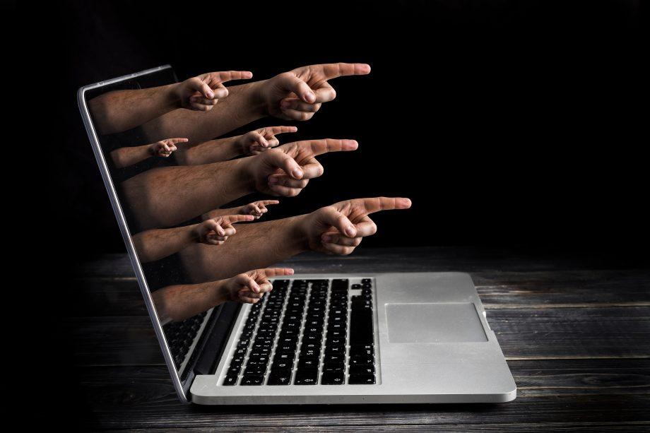 Fotomontage von Zeigefingern, die aus einem Laptop-Display rageb