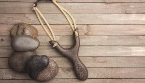 Steinschleuder neben Steinen auf Holzuuntergrund