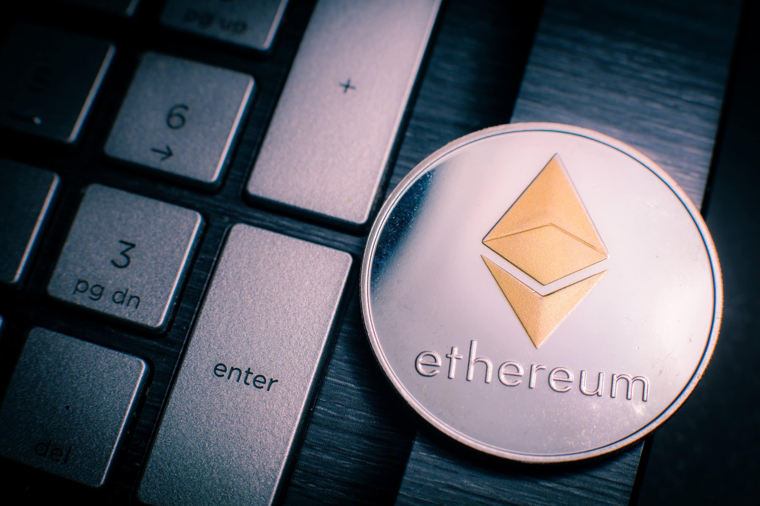 Eine physische Ethereum-Münze neben einer Tastatur.