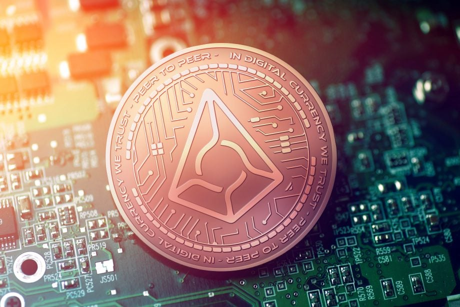 glänzende Kupfer-AUGUR-Kryptowährungsmünze auf unscharfem Motherboard-Hintergrund